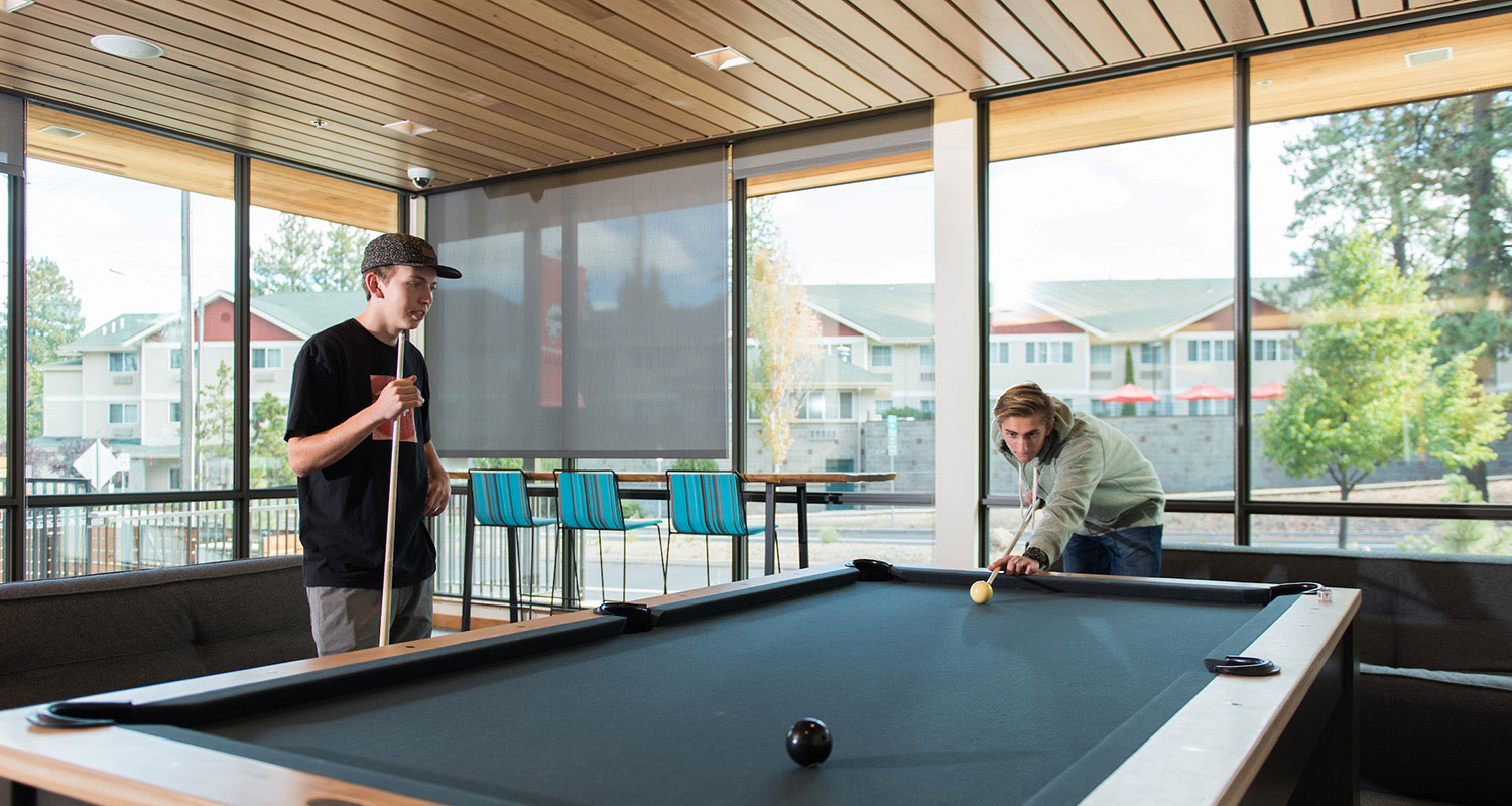 Students playing pool in the residence hall.