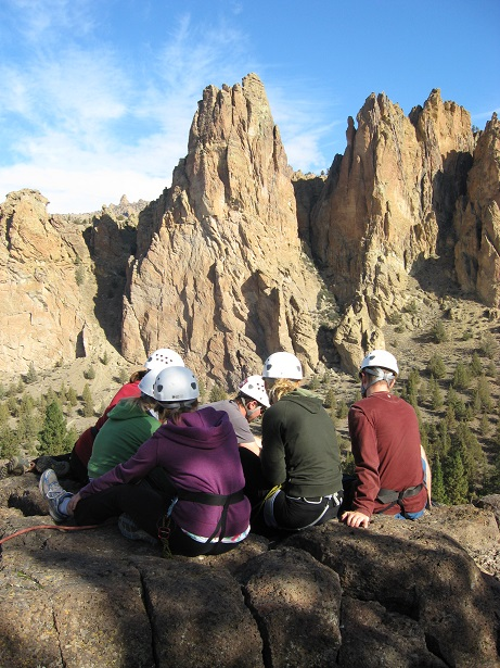 Group of student learning anchor building with Smith Rock tuft formations in the background