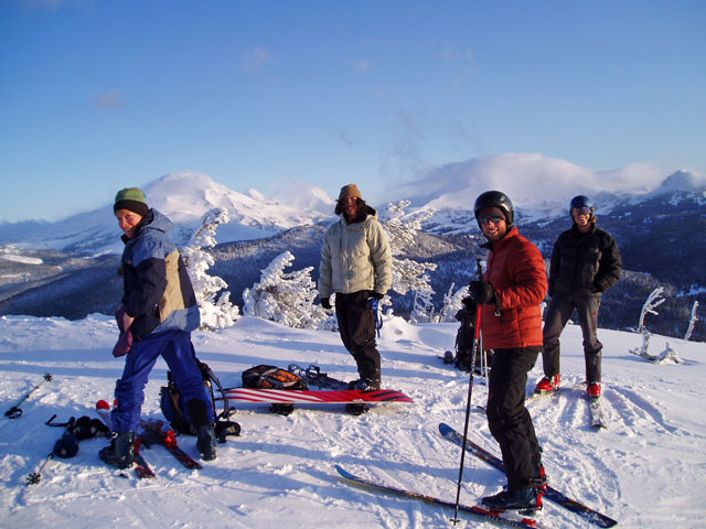 Preparing to descend a mountain on skis and snowboards with the 3 sisters in the background