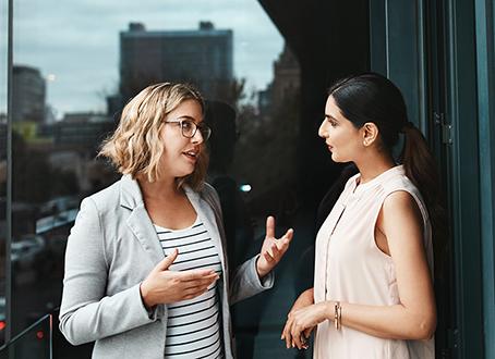 Two women talking on an outside deck
