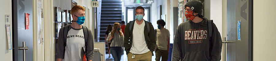 Students walking in Tykeson Hall wearing face masks